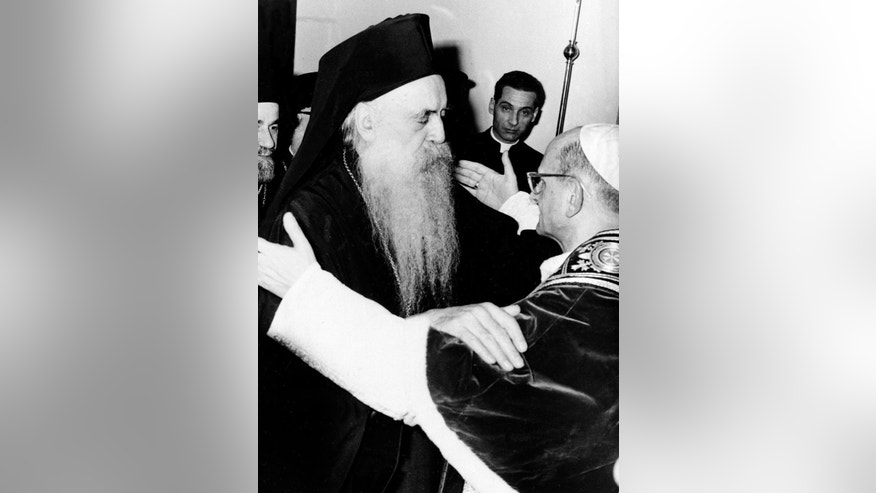 "FILE -- In this file photo taken on Jan. 5, 1964, Pope Paul VI, right, and orthodox Patriarch Athenagoras of Constantinople embrace at their historic meeting at the apostolic delegation's headquarters on the Mount of Olives in Jerusalem, Jordan. The iconic 1964 embrace between the diminutive Paul and the six-foot-tall, bearded Patriarch of Constantinople ended 900 years of mutual excommunications and divisions between Catholic and Orthodox stemming from the Great Schism of 1054, which split Christianity. Pope Francis insists his weekend pilgrimage to the Middle East is a ""strictly religious"" commemoration of a key turning point in Catholic-Orthodox relations. But the three-day visit is the most delicate mission of his papacy and will test his diplomatic chops as he negotiates Israeli-Palestinian tensions and fallout from Syria's civil war. (AP Photo)"