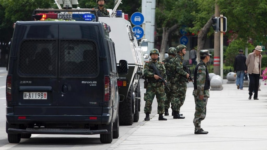 Armed Paramilitary policemen stand guard next to their Armored personnel carrier parked near the People's Square in Urumqi, China's northwestern region of Xinjiang, Friday, May 23, 2014. A day after the attack in Xinjiang's capital of Urumqi, survivors told of their terror during the attack and said they no longer feel insulated from a long-simmering insurgency against Chinese rule, which has struck their city twice in recent weeks. While the perpetrators haven't been named, Chinese authorities have blamed recent attacks on radical separatists from the country's Muslim Uighur minority. (AP Photo/Andy Wong)
