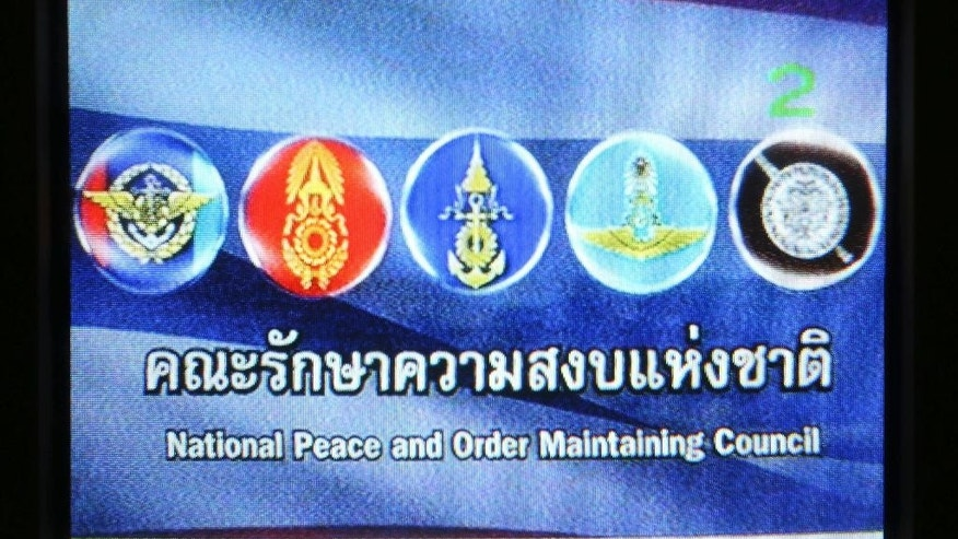 This photo taken off the TV screen shows the blue screen with military crests that replaced all TV programming in Thailand Friday, May 23, 2014. Thailand's junta has commandeered every TV channel for round-the-clock broadcasts of dour announcements and patriotic hymns. The public's verdict: DJ, please change the soundtrack. (AP Photo/Apichart Weerawong)