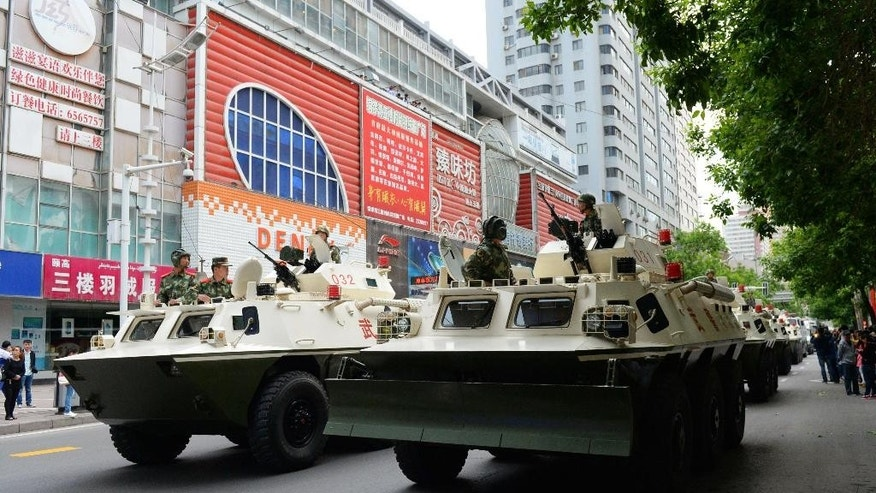 In this Friday, May 23, 2014 photo, paramilitary policemen on their armored vehicles parade on a street in Urumqi, China's northwestern region of Xinjiang. Authorities on Saturday announced the first arrest in a bombing in China's Muslim northwest and said they were launching a yearlong anti-terrorism crackdown. (AP Photo/Kyodo News) JAPAN OUT, CREDIT MANDATORY
