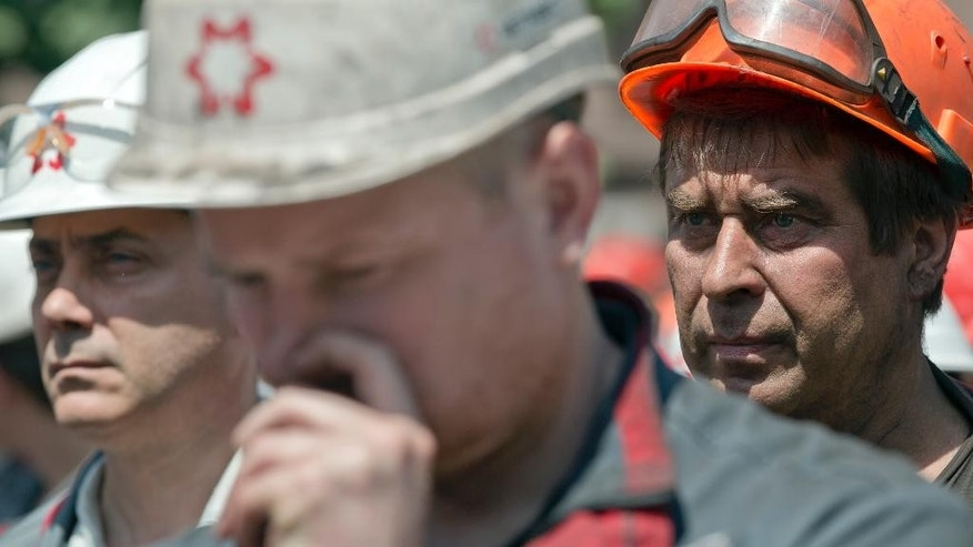In this picture taken on Thursday, May 22, 2014, workers of Illich Iron & Steel Works steel plant gather for an anti-war protest, supported by the management, in Mariupol, eastern Ukraine. In the roiling debate over eastern Ukraine, where pro-Russian separatist attacks have turned increasingly bloody, neither the country's richest man nor some of his dirt-poor compatriots have much time for patriotism, ethnic feuding or political parties.  (AP Photo/Vadim Ghirda)