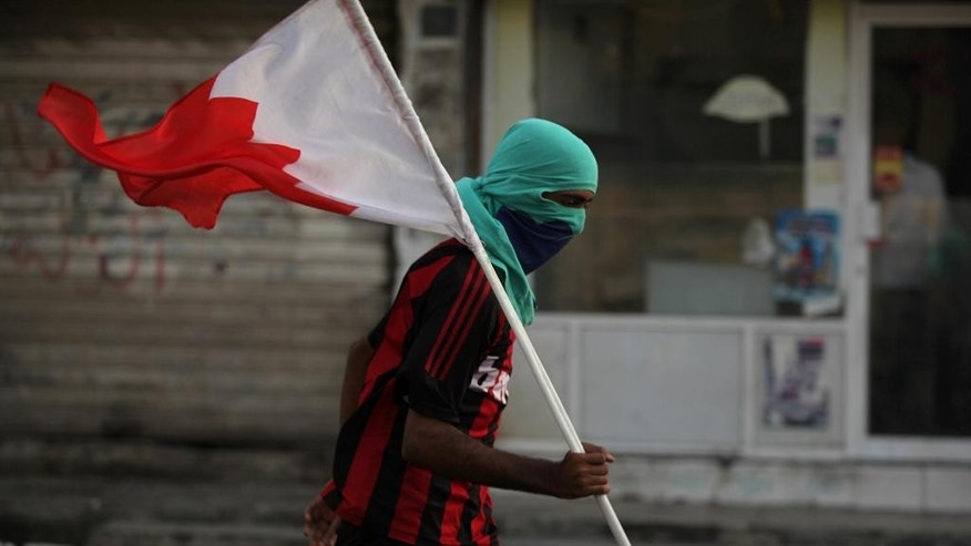 A Bahraini anti-government protester carrying a Bahraini flag runs from riot police during clashes in Diraz, Bahrain, Friday, May 23, 2014. Clashes erupted in several northern towns after last-minute notification that a planned opposition rally would not be authorized by authorities. Tensions are high in the Gulf island kingdom, following two recent deaths of protesters and delays in releasing the body of another man who died earlier. (AP Photo/Hasan Jamali)