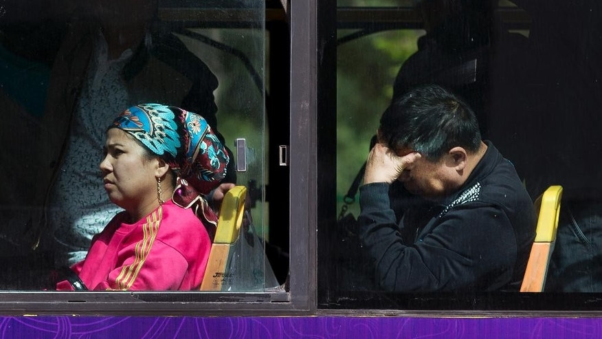 In this Friday, May 23, 2014 photo, a Chinese man, right, sits behind an ethnic Uighur woman inside a public bus in Urumqi, China's northwestern region of Xinjiang. State media say ethnic Chinese and minorities mix easily in Urumqi, capital of the Xinjiang region. But interviews with more than two dozen residents following Thursday's bombing at a vegetable market that killed at least 43 people suggest a harsher reality in which the two groups regard each other across a tense gulf of misunderstanding and suspicion. Relations have deteriorated since rioting in 2009 left nearly 200 people dead. Both groups are moving out of ethnically mixed neighborhoods, making an already divided city of 3 million people even more segregated. (AP Photo/Andy Wong)
