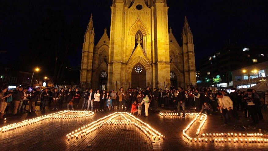 People light candles with the word peace written in Spanish, during a vigil for peace called by the Social Party of National Unity, that supports the re-election of President Juan Manuel Santos, in Bogota, Colombia, Thursday, May 22, 2014. Colombia will hold elections on May 25. (AP Photo/Javier Galeano)