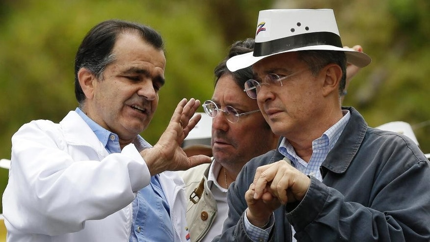 FILE - In this May 10, 2014 file photo, Democratic Center presidential candidate Oscar Ivan Zuluaga, left, talks to former President Alvaro Uribe, right, and former vice-president Francisco Santos, center, during a campaign rally in Bogota, Colombia. Accusations of bribes from drug traffickers, spying and email hacking have turned Colombia's presidential election into an ugly slugfest that has further polarized a country trying to emerge from its violent past. Much of the blame for the dirty campaigning falls on two former allies whose public feuding has divided Colombia the past four years: President Juan Manuel Santos and his still powerful predecessor, Uribe. (AP Photo/Fernando Vergara)