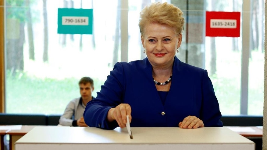 CORRECTS DATE - Lithuania's President Dalia Grybauskaite and presidential candidate, casts her vote at a polling station during the second round of voting in presidential elections in Vilnius, Lithuania, Sunday, May 25, 2014. Polls have opened in Lithuania for the second round of the presidential election, in which incumbent Grybauskaite is competing against the center-left candidate Zigmantas Balcytis. (AP Photo/Mindaugas Kulbis)
