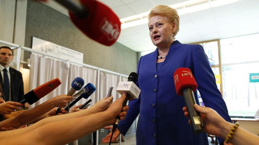 CORRECTS DATE -  Lithuania's President Dalia Grybauskaite and presidential candidate, speaks to the members of press at a polling station during the second round of voting in presidential elections in Vilnius, Lithuania, Sunday, May 25, 2014. Polls have opened in Lithuania for the second round of the presidential election, in which incumbent Grybauskaite is competing against the center-left candidate Zigmantas Balcytis. (AP Photo/Mindaugas Kulbis)