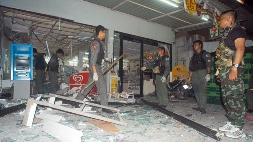 May 24, 2014: Thai police officers and soldiers examine the site where a bomb exploded at a super store in Pattani province, southern Thailand. (AP Photo/Sumeth Panpetch)