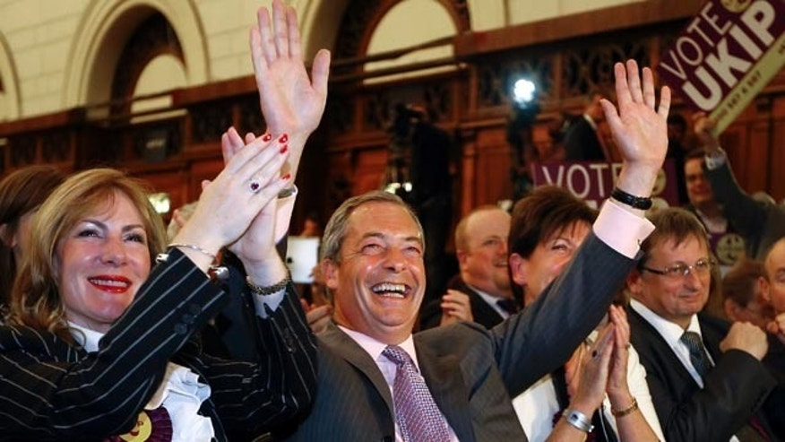 May 26, 2014: Nigel Farage leader of Britain's UK Independence Party (UKIP) celebrates with candidate Janice Atkinson, left, as he hears the results of the south east region European Parliamentary Election vote at the Guildhall in Southampton, England. (AP Photo/Kirsty Wigglesworth)