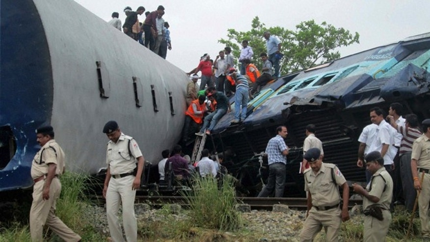 May 26, 2014: Indian officials and rescuers gather around the wreckage after the Gorakhpur Express passenger train slammed into a parked freight train Chureb, near Basti, Uttar Pradesh state, India. (AP)