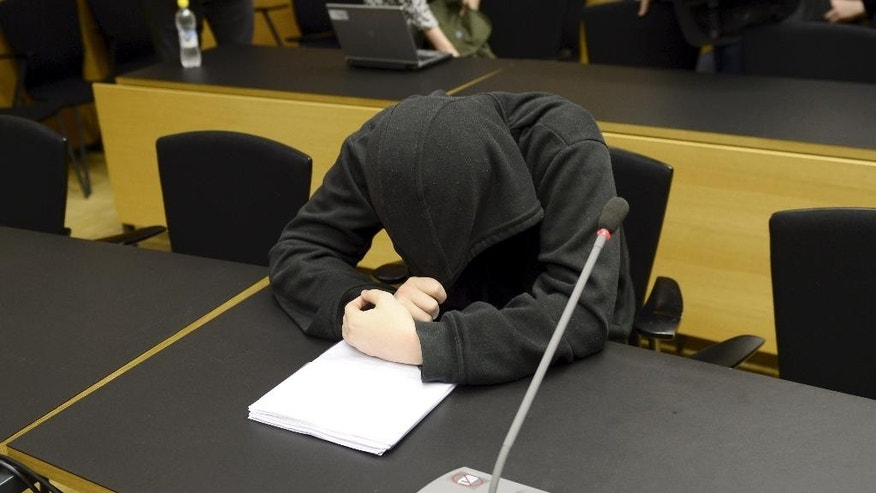 An unidentified man, bows his head, at a court hearing, in Helsinki, Finland, Monday, May 26, 2014. A man and a woman are being tried for planning an attack at the University of Helsinki with the aim of killing several people and for possessing weapons to carry out the slaughter. The case opened Monday at Helsinki District Court against the suspects, who were not named. They were not students at the university. (AP Photo/Lehtikuva, Antti Aimo-Koivisto)  FINLAND OUT