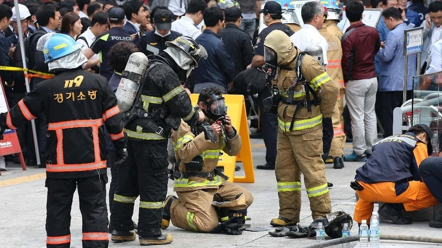 South Korean firefighters check their equipments at the bus terminal at Goyang, north of Seoul, South Korea, Monday, May 26, 2014. A fire at a bus terminal near Seoul on Monday left seven people dead and 20 others injured, emergency officials said. (AP Photo/Yonhap, Park Ji-ho) KOREA OUT