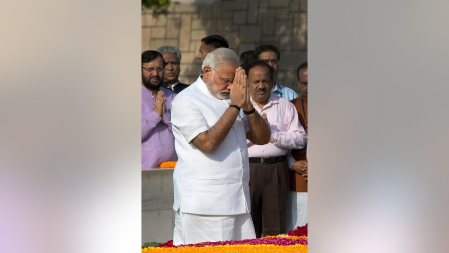 Indian Prime Minister-designate and Hindu nationalist Bharatiya Janata Party  leader Narendra Modi pays his respects at Rajghat, the memorial of Mahatma Gandhi, in New Delhi, India, Monday, May 26, 2014. Modi, 63, will be sworn-in as the India's Prime Minister on Monday evening by President Pranab Mukherjee at the forecourt of the Indian presidential palace. (AP Photo /Manish Swarup)