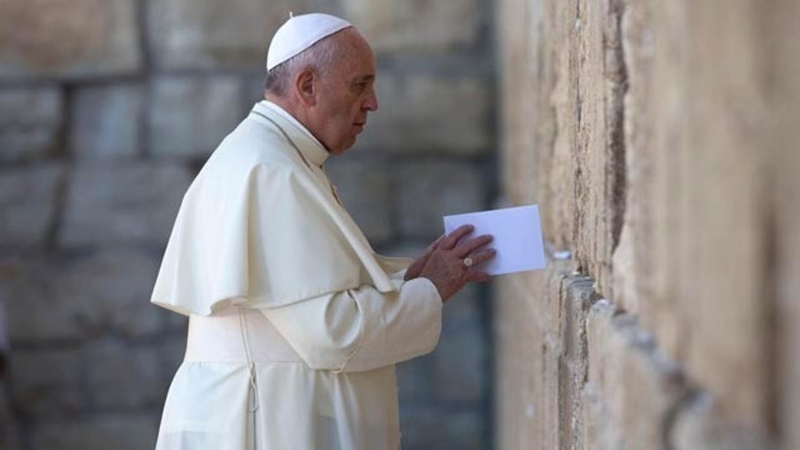 May 26, 2014: Pope Francis places an envelope in on of the cracks between the stones of the Western Wall, the holiest place where Jews can pray, in the Old City of Jerusalem, Israel. (AP Photo/Andrew Medichini, Pool)