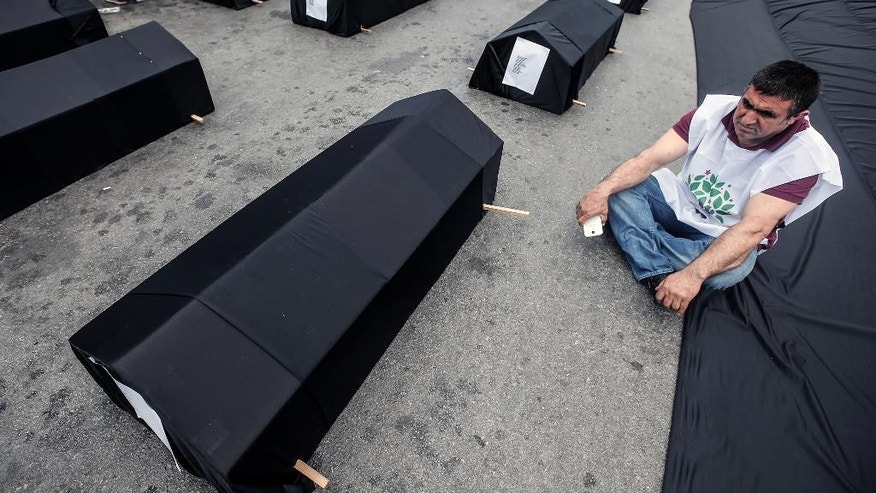 A man sits next to mock coffins for the victims before thousands of people march to protest the Soma mine disaster that killed 301 miners last week, in Istanbul, Turkey, Sunday, May 25, 2014. (AP Photo/Emrah Gurel)