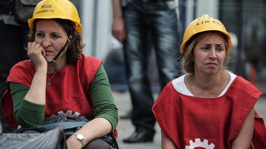 Two women watch as thousands of people demonstrate to protest the Soma mine disaster that killed 301 miners last week, in Istanbul, Turkey, Sunday, May 25, 2014. (AP Photo/Emrah Gurel)