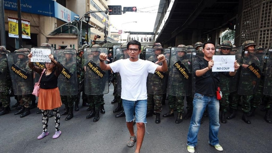 """Protesters walk durng an anti-coup demonstration in front of line of Thai soldiers in Bangkok, Thailand Sunday, May 25, 2014. A spokesman for Thailand's coup leaders said Sunday that democracy had caused """"losses"""" for the country, as the junta sought to combat growing international condemnation and hundreds of protesters angrily confronted soldiers in central Bangkok. (AP Photo/Wason Wanichakorn)"""