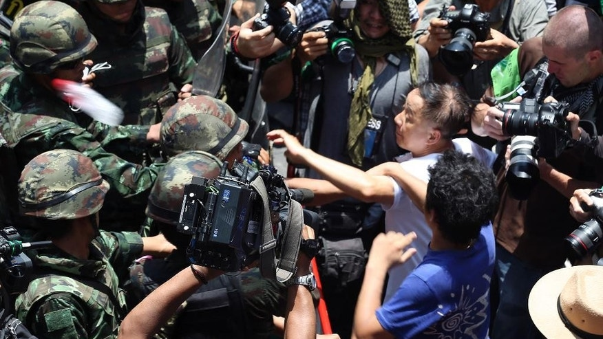 """Protesters, right, scuffle with Thai soldiers during an anti-coup demonstration outside a shopping mall in Bangkok, Thailand Sunday, May 25, 2014. A spokesman for Thailand's coup leaders said Sunday that democracy had caused """"losses"""" for the country, as the junta sought to combat growing international condemnation and hundreds of protesters angrily confronted soldiers in central Bangkok. (AP Photo/Apichart Weerawong)"""