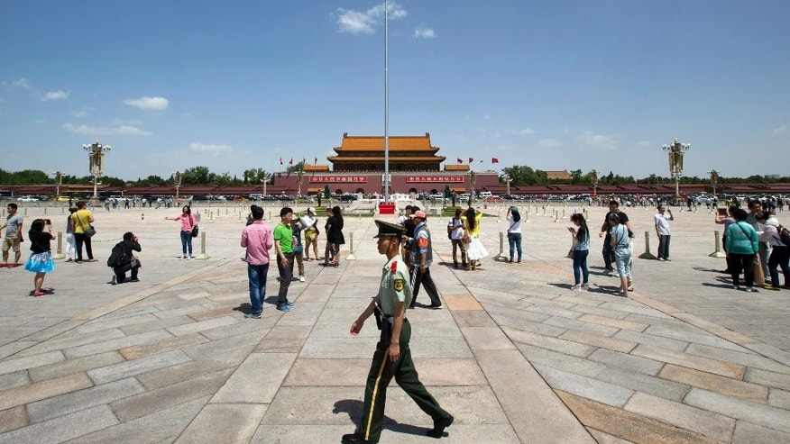 A paramilitary policeman patrols on Tiananmen Sqaure in Beijing, China, Tuesday, May 27, 2014. In prosecuting the country's political and social activists, an image-conscious Beijing is shifting its tactics. (AP Photo/Alexander F. Yuan)