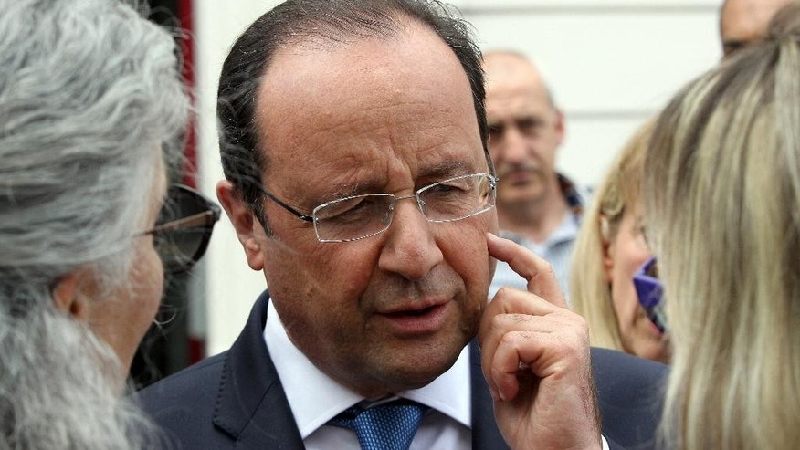 French President Francois Hollande discusses with people after voting for the European elections in Tulle, central France, Sunday, May 25, 2014. Voters of 21 nations are casting ballots to decide the makeup of the next European Parliament and help determine the European Union's future leaders and direction. (AP Photo/Bob Edme)