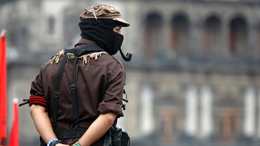 FILE - In this May 28, 2006 file photo, Subcomandante Marcos looks out into the Zocalo, Mexico City's main plaza, in Mexico. Marcos announced Sunday May 25, 2014, that he no longer is the official spokesperson of the Zapatista rebel movement. (AP Photo/Gregory Bull)