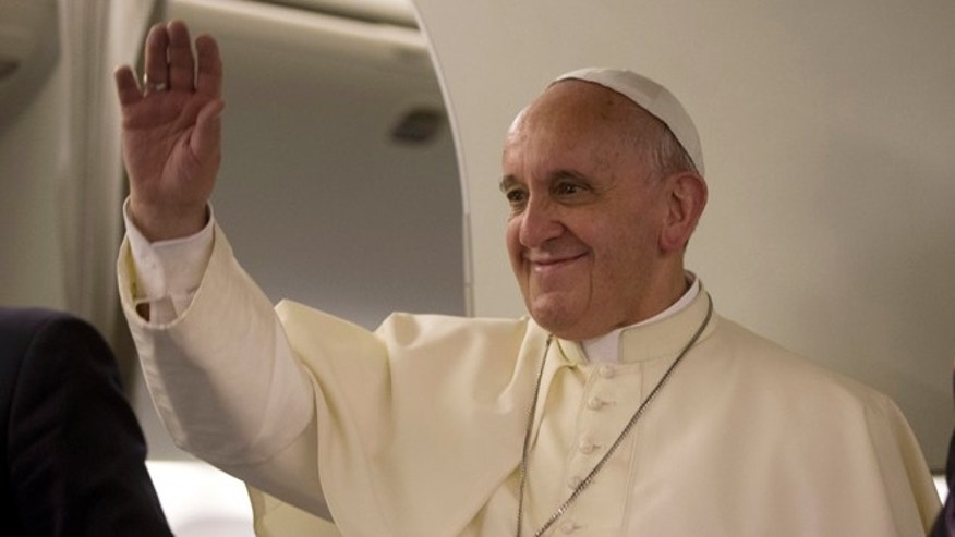 Pope Francis waves to journalists as he arrives for a press conference he held aboard the papal flight on his way back to Rome at the end of a three day trip to the Midle East, Monday, May 26, 2014 (AP Photo/Andrew Medichini, Pool)