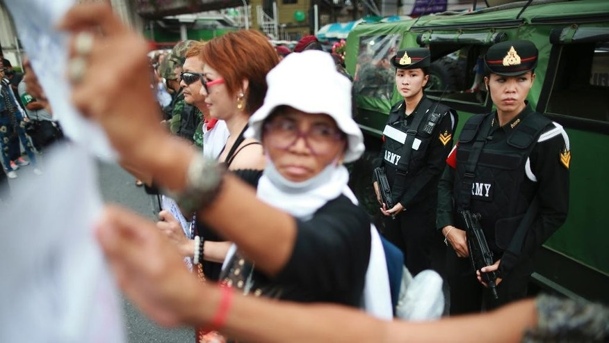 Thai female military police officers guard as protesters stage an anti-coup demonstration at the Victory Monument square in Bangkok, Thailand Tuesday, May 27, 2014. Armed troops detained a Thai Cabinet minister who defiantly emerged from hiding on Tuesday to condemn last week's military coup and urge a return to civilian rule, in the first public appearance by any member of the ousted government. (AP Photo/Wason Wanichakorn)