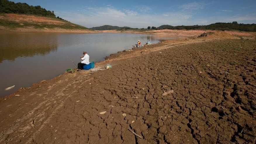 In this May 14, 2014 photo, people fish at the Jaguari dam, which is part of the Cantareira System, responsible for providing water to the Sao Paulo metropolitan area, in Braganca Paulista, Brazil. The worst drought in more than 80 years is hitting Sao Paulo, Brazil's largest city just as it prepares for the tens of thousands of foreigners expected at the tournament opener. (AP Photo/Andre Penner)