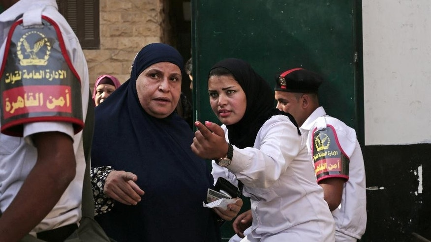 An Egyptian policewoman directs a voter to a polling station during the second day of voting in the presidential election in Cairo, Egypt, Tuesday, May 27, 2014. State TV says Egypt's election commission has extended voting in the presidential election for a third day amid reported low turnout. Government officials, media and the military harangued voters to go to the polls Tuesday in what was supposed to be the final day of the vote, worried that turnout was weaker than expected. The front-runner, former army chief Abdel-Fattah el-Sissi, is trying to garner an overwhelming show of support. (AP Photo/Nariman El-Mofty)
