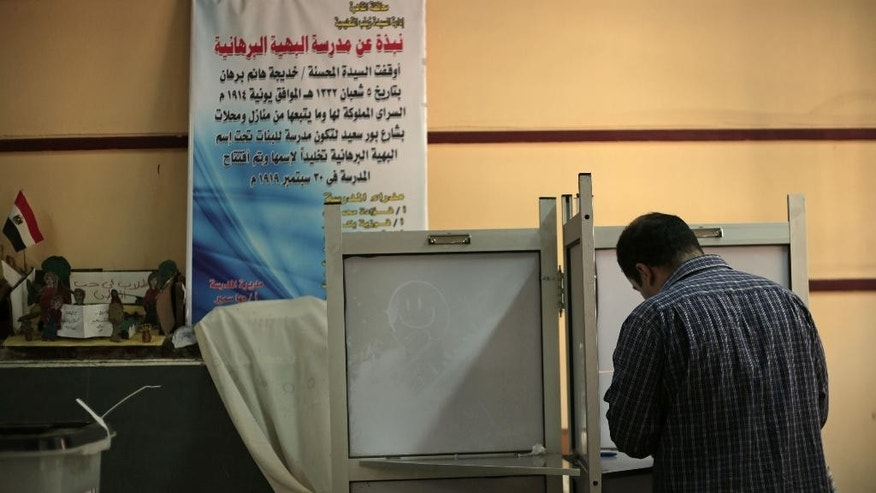 A man votes during the second day of voting in the presidential election, in Cairo, Egypt, Tuesday, May 27, 2014. State TV says Egypt's election commission has extended voting in the presidential election for a third day amid reported low turnout. Government officials, media and the military harangued voters to go to the polls Tuesday in what was supposed to be the final day of the vote, worried that turnout was weaker than expected. The front-runner, former army chief Abdel-Fattah el-Sissi, is trying to garner an overwhelming show of support. (AP Photo/Nariman El-Mofty)