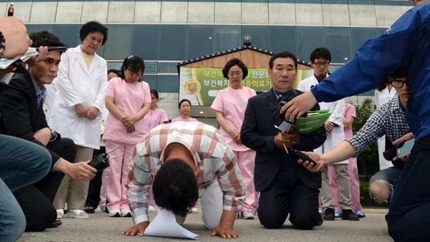 May 28, 2014: Hospital employees kneel and bow to apologize for victims of a fire outside of a hospital in Jangseong, South Korea. (AP Photo/Yonhap, Hyung Min-woo)