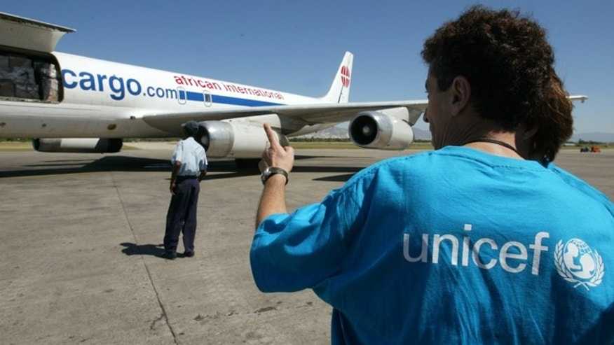 In this file photo, a UNICEF staffer supervises the unloading of a planeload of aid at the Port-au-Prince airport.