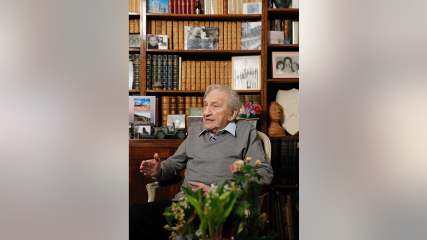 In this photo dated Thursday May 8, 2014, Bernard Dargols talks,  during an interview with the Associated Press at his home in La Garenne-Colombes, outside Paris, France. When he left Paris at age 18, the plan was to go to New York for a year and learn his father's sewing machine trade. Six years later, Bernard Dargols found himself crossing the Channel in a U.S. Army uniform, sloshing ashore on Omaha Beach to a homeland that had persecuted his Jewish family. (AP Photo/Christophe Ena)