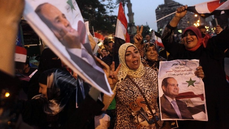 Supporters of presidential candidate former army chief Abdel-Fattah el-Sissi hold his posters and wave national flags as they celebrate during the second day of presidential elections in Cairo, Egypt, Tuesday, May 27, 2014. Egypt extended its presidential election an extra day after two days of reportedly low voter turnout, an embarrassment to attempts by the front-runner, El-Sissi, to garner an overwhelming show of public support. (AP Photo/Amr Nabil)