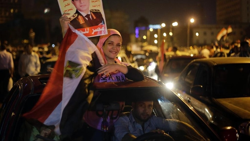 "A supporter of presidential hopeful Abdel-Fattah el-Sissi, Egypt's former military chief, holds his poster and a national flag during a celebration at Tahrir Square in Cairo, Egypt, Thursday, May 29, 2014. El-Sissi appeared well on his way to a landslide victory over his sole opponent, according to partial election results announced late Wednesday, after voting was extended for a third day in an attempt to prevent an embarrassment over low turnout. Arabic reads ""Egypt for all Egyptians.""(AP Photo/Amr Nabil)"