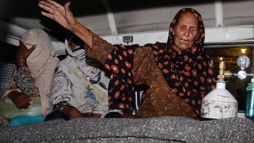 May 27, 2014: A family member of a pregnant woman who was stoned to death by her own family wails over her dead body in an ambulance at a local hospital in Lahore, Pakistan. (AP)