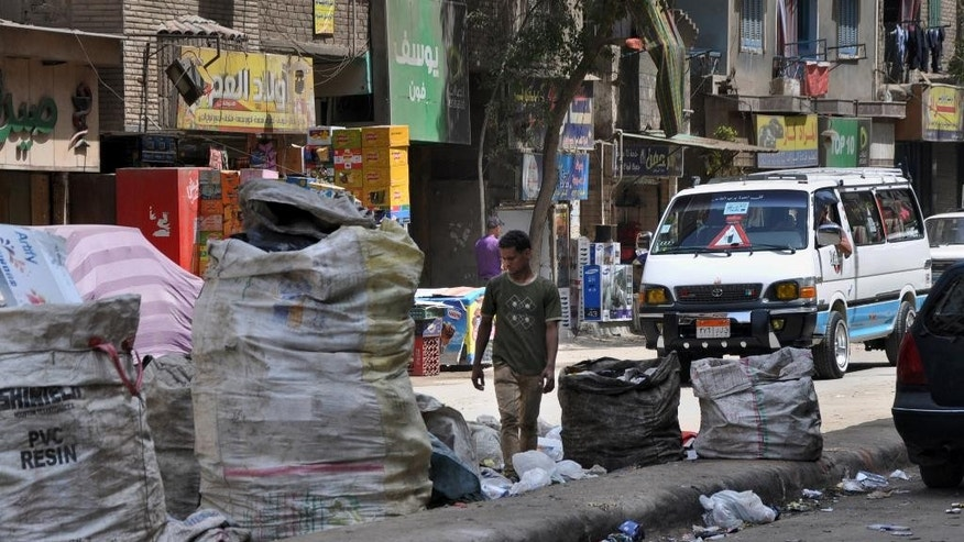 "A man walks through garbage left on a street in Cairo's neighborhood of Dar el-Salam, Egypt, Thursday, May 29, 2014. ""El-Sissi will leave no one wanting!"" the 50-year-old shopkeeper in a Cairo slum barked when a younger man criticized the victor of Egypt's presidential election, former army chief Abdel-Fattah el-Sissi. The heated argument shows the limits of the retired field marshal's landslide amid a generational divide. Many older voters embraced him enthusiastically. But among the young, ambitions for change have been unleashed, and even those who voted for el-Sissi have low expectations he will fulfill them. (AP Photo/Mahmoud Bakkar)"