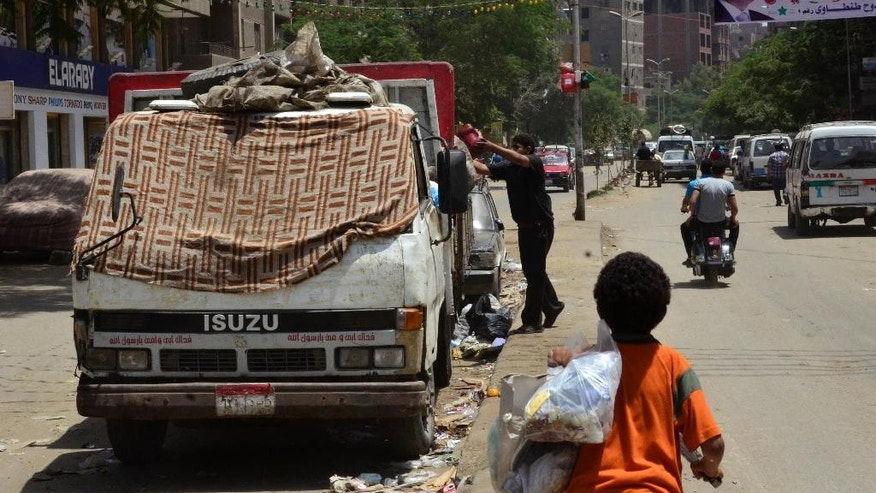 "A boy walks by a truck where a man collects garbage from a street in Cairo's neighborhood of Dar el-Salam, Egypt, Thursday, May 29, 2014. ""El-Sissi will leave no one wanting!"" the 50-year-old shopkeeper in a Cairo slum barked when a younger man criticized the victor of Egypt's presidential election, former army chief Abdel-Fattah el-Sissi. The heated argument shows the limits of the retired field marshal's landslide amid a generational divide. Many older voters embraced him enthusiastically. But among the young, ambitions for change have been unleashed, and even those who voted for el-Sissi have low expectations he will fulfill them. (AP Photo/Mahmoud Bakkar)"
