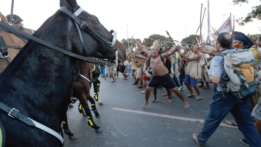 Indians clash with military police during a protest against the FIFA World Cup outside the National Stadium in Brasilia, Brazil, Tuesday, May 27, 2014. Brazil's indigenous communities calling for the federal court to demarcate indigenous lands are also protesting against the 2014 FIFA World Cup that starts in June. (AP Photo/Eraldo Peres)