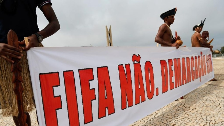"Indians hold a poster that reads in Portuguese ""FIFA No. Demarcation of Indian lands yes."" at protest outside the Supreme Court in Brasilia, Brazil, Tuesday, May 27, 2014. Brazil's indigenous communities calling for the federal court to demarcate indigenous lands are also protesting against the 2014 FIFA World Cup that starts in June. (AP Photo/Eraldo Peres)"