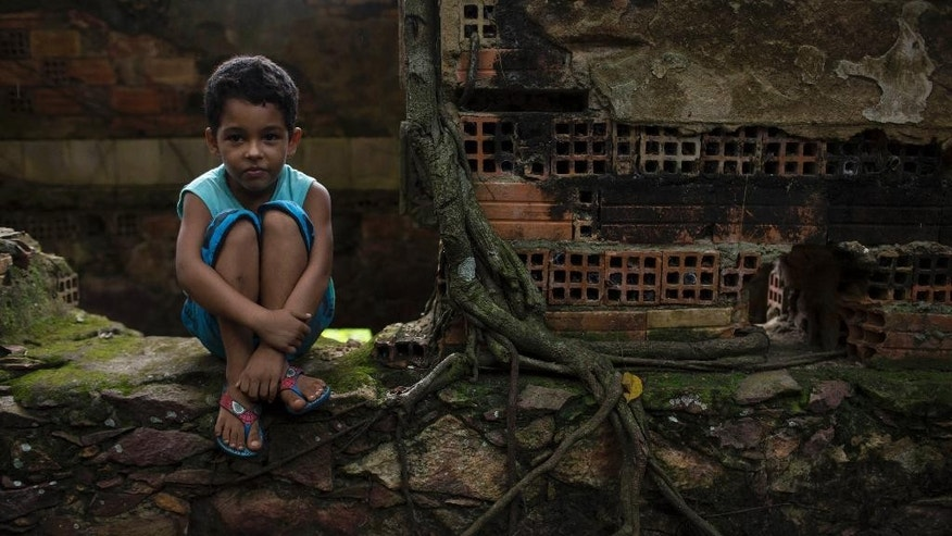 In this May 21, 2014 photo, a boy watches a soccer match as he waits for his turn to play in the ruins of Paricatuba, near Manaus, Brazil. Paricatuba was built in 1898 at the height of the region's rubber boom, which briefly transformed Manaus into one of the richest cities in the world. The sprawling villa was initially intended to house the Italian immigrants who arrived to work in the rubber trade. (AP Photo/Felipe Dana)