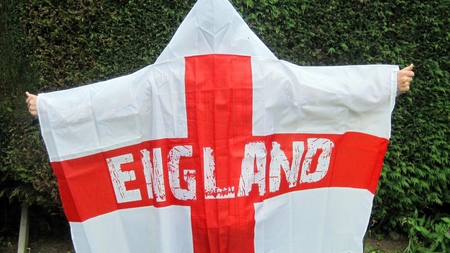 A man models a wearable England flag, made by Asda, in London, Friday, May 30, 2014. British supermarket chain Asda has been criticized for launching a wearable England flag ahead of the World Cup that some customers say resembles an outfit worn by U.S. far-right organization the Ku Klux Klan. Designers of the flag _ a St. George's Cross with the word 'England' on it _ included a white hood so fans could stay dry while wearing it. (AP Photo/PA, Carmel Wilkinson) UNITED KINGDOM OUT