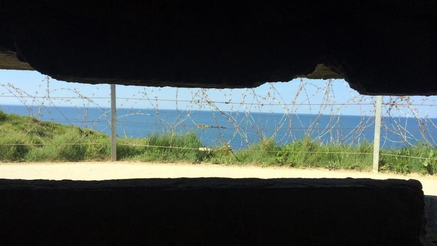 In this photo dated May 15, 2014, the Pointe du Hoc is seen from inside a German bunker in Cricqueville en Bessin, in Normandy, France. Andree Auvray, nine months pregnant, was hiding from German bombings in a Normandy ditch with her husband one night in June 1944 when their dogs started barking. The shadows of three soldiers appeared. The soldiers were Americans. D-Day had begun. In an interview with Associated Press, Auvray relives that wrenching time with clarity and a growing sense of urgency. Seventy years have passed since the Allied invasion of Normandy helped turn the tide against Hitler. With their numbers rapidly diminishing, she and other French women and men who owe their freedom to D-Day's fighters are more determined than ever to keep alive the memory of the battle and its meaning. (AP Photo/Nicolas Garriga)