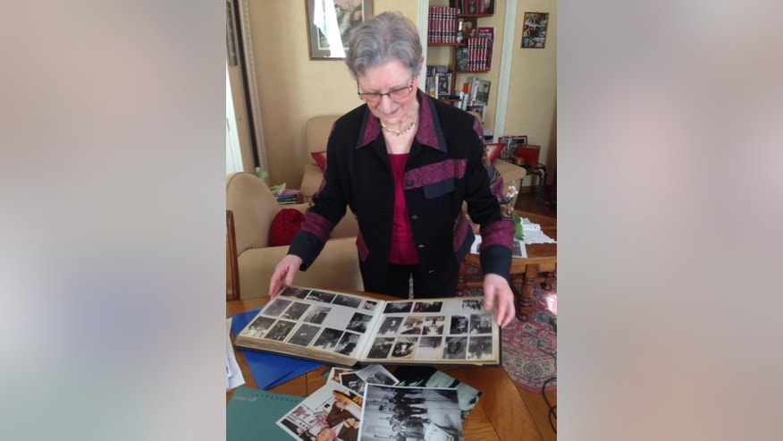 In this photo dated May 14, 2014, Andree Auvray displays her family album during an interview with the Associated Press in Sainte Mere Eglise in Normandy, France. Andree Auvray, nine months pregnant, was hiding from German bombings in a Normandy ditch with her husband one night in June 1944 when their dogs started barking. The shadows of three soldiers appeared. The soldiers were Americans. D-Day had begun. Auvray relives that wrenching time with clarity and a growing sense of urgency. Seventy years have passed since the Allied invasion of Normandy helped turn the tide against Hitler. With their numbers rapidly diminishing, she and other French women and men who owe their freedom to D-Day's fighters are more determined than ever to keep alive the memory of the battle and its meaning. (AP Photo/Catherine Gaschka)