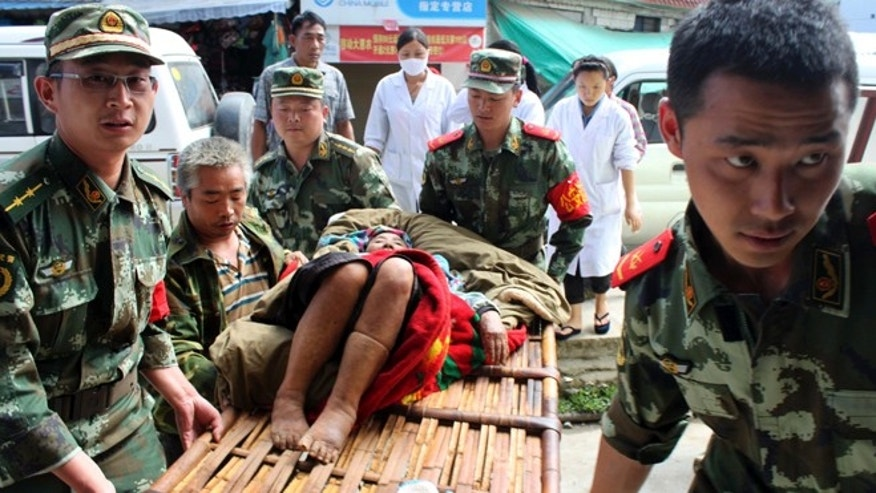 May 30, 2014: In this photo released by China's Xinhua news agency, rescuers carry a survivor after a major earthquake hit Yingjiang County in southwest China's Yunnan Province.