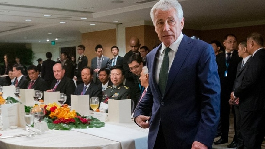 May 31, 2014: US Defense Secretary Chuck Hagel walks to his seat as he arrives for the official luncheon at the 13th Asia Security Summit in Singapore.