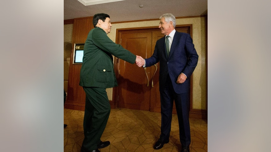 U.S. Defense Secretary Chuck Hagel, right, greets Vietnam's Defense Minister Phung Quang Thanh, left, before their meeting, Saturday, May 31, 2014 in Singapore. Hagel traveled to Singapore to attend the 13th Asia Security Summit. (AP Photo/Pablo Martinez Monsivais, Pool)
