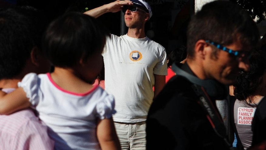 A man shields his eyes from the sun during a first gay pride parade in downtown Nicosia, Cyprus, Saturday, May 31, 2014. Cyprus decriminalized homosexuality 12 years ago, but activists say the country still lags behind in providing equal rights to homosexuals regarding civil partnerships. (AP Photo/Petros Karadjias)