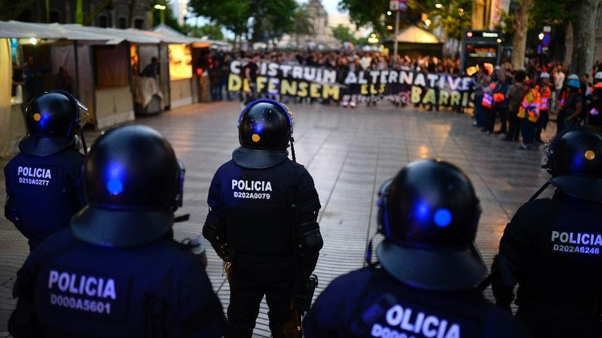 Riot police take position during a protest against the eviction of squatters in Barcelona, Spain, Saturday, May 31, 2014. The demonstration, which drew supporters from around and outside the city, was to protest Monday's closing of a social center that was occupied by squatters for 17 years. (AP Photo/Manu Fernandez)
