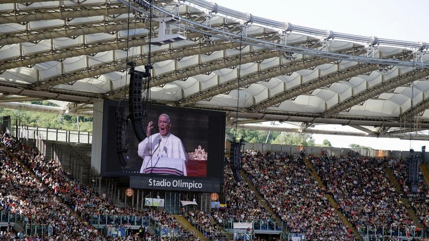 The image of Pope Francis is projected on a giant screen as he delivers his speech during a meeting at Rome's Olympic stadium, Sunday, June 1, 2014. (AP Photo/Gregorio Borgia)